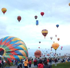 Hundreds of gaily colored and fancy shaped balloons take to the skies over Albuquerque during the Albuquerque International Balloon Fiesta.  Look closely and you will see the Pepsi can and a football floating by.